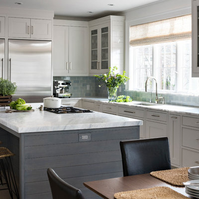 Transitional l-shaped eat-in kitchen photo in New York with an undermount sink, white cabinets, blue backsplash, subway tile backsplash, stainless steel appliances, an island and recessed-panel cabinets