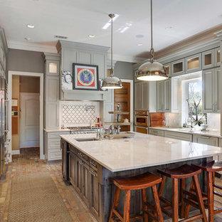 Ejemplo de cocina en U, clásica renovada, con armarios con rebordes decorativos, puertas de armario grises, una isla, salpicadero blanco, electrodomésticos de acero inoxidable y suelo de ladrillo