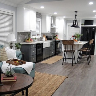 Small country l-shaped open plan kitchen in Other with a farmhouse sink, shaker cabinets, white cabinets, quartzite benchtops, grey splashback, subway tile splashback, black appliances, vinyl floors, with island, grey floor and white benchtop.