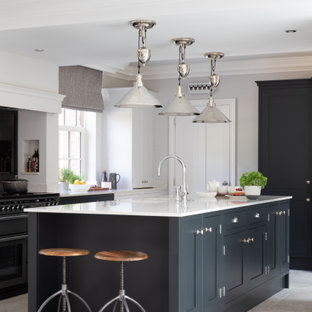 This is an example of a large classic u-shaped kitchen in Other with a submerged sink, shaker cabinets, black cabinets, an island, grey floors and white worktops.