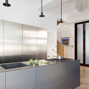 Inspiration for a mid-sized contemporary galley kitchen in London with an integrated sink, medium hardwood floors, flat-panel cabinets, stainless steel cabinets, with island and granite benchtops.