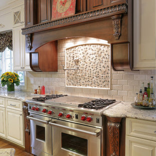 Inspiration for a farmhouse medium tone wood floor kitchen remodel in New York with raised-panel cabinets, granite countertops, stone tile backsplash, white cabinets, beige backsplash and stainless steel appliances