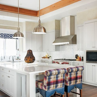 Southwestern kitchen designs - Southwest l-shaped dark wood floor and brown floor kitchen photo in Other with shaker cabinets, white cabinets, white backsplash, subway tile backsplash, white appliances and an island
