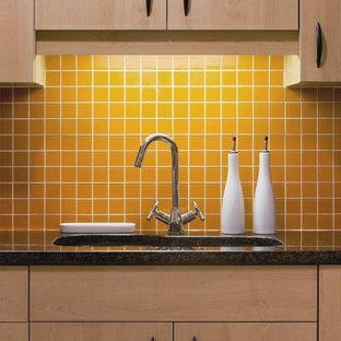 Immagine di una cucina eclettica con paraspruzzi giallo