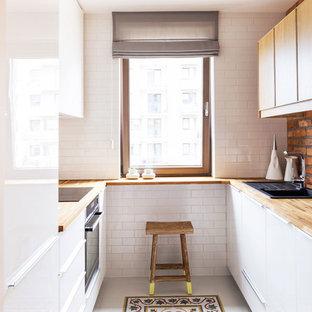 На фото: маленькая параллельная кухня в скандинавском стиле с плоскими фасадами, белыми фасадами, столешницей из дерева, белым фартуком, фартуком из плитки кабанчик и техникой из нержавеющей стали без острова с