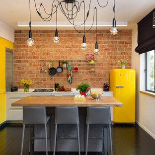 Diseño de cocina en L, ecléctica, pequeña, cerrada, con una isla, armarios con paneles lisos, puertas de armario amarillas, electrodomésticos de colores y suelo de madera pintada