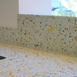 Imagen de cocina moderna, pequeña, con armarios con paneles lisos, puertas de armario grises, encimera de vidrio reciclado, península y encimeras amarillas