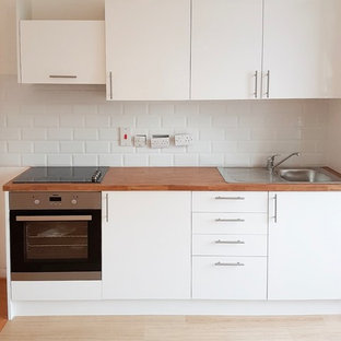 Small scandinavian l-shaped eat-in kitchen in Surrey with glass-front cabinets, white cabinets, wood benchtops, stainless steel appliances, linoleum floors, no island and beige benchtop.