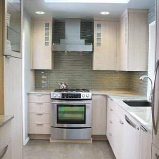 Cette photo montre une cuisine tendance en U fermée avec un placard à porte plane, un électroménager en acier inoxydable, un plan de travail en granite, un évier encastré, des portes de placard en bois clair, une crédence verte et une crédence en carreau de verre.