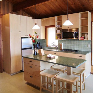 Kitchen in Seattle with an undermount sink, flat-panel cabinets, light wood cabinets, recycled glass benchtops, green splashback, glass tile splashback, stainless steel appliances, linoleum floors and with island.