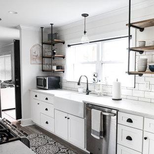 マイアミの小さいカントリー風おしゃれなII型キッチン (シェーカースタイル扉のキャビネット、白いキャビネット、クオーツストーンカウンター、白いキッチンパネル、アイランドなし、白いキッチンカウンター、エプロンフロントシンク、サブウェイタイルのキッチンパネル、シルバーの調理設備の、茶色い床) の写真