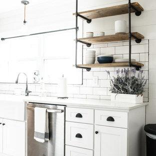 Foto på ett litet lantligt vit kök, med en rustik diskho, skåp i shakerstil, vita skåp, bänkskiva i kvarts, vitt stänkskydd, stänkskydd i keramik, rostfria vitvaror, laminatgolv och brunt golv