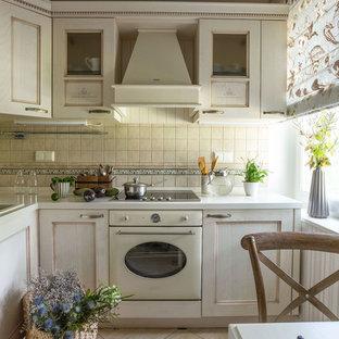 Immagine di una cucina a L tradizionale chiusa con lavello da incasso, ante con riquadro incassato, ante bianche, paraspruzzi beige, elettrodomestici bianchi e nessuna isola