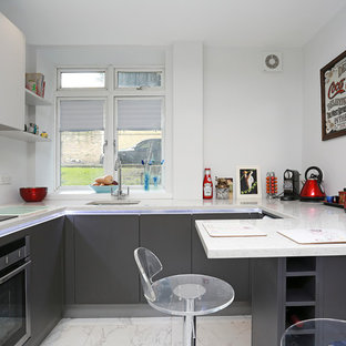 Small minimalist kitchen photo in London with flat-panel cabinets, gray cabinets and stainless steel appliances