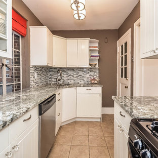 Enclosed kitchen - small traditional galley enclosed kitchen idea in New York with an undermount sink, white cabinets, granite countertops, gray backsplash, mosaic tile backsplash, stainless steel appliances and no island