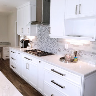 Small traditional enclosed kitchen ideas - Inspiration for a small timeless galley porcelain tile and brown floor enclosed kitchen remodel in Los Angeles with an undermount sink, recessed-panel cabinets, white cabinets, quartz countertops, gray backsplash, glass tile backsplash, stainless steel appliances and no island