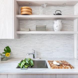 Ejemplo de cocina de galera, escandinava, pequeña, cerrada, sin isla, con armarios con paneles lisos, puertas de armario con efecto envejecido, encimera de cuarcita, salpicadero gris, salpicadero de azulejos en listel, electrodomésticos con paneles y encimeras verdes