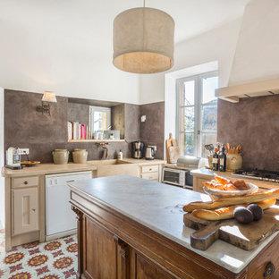 Cette photo montre une cuisine méditerranéenne en L fermée avec un évier de ferme, des portes de placard beiges, une crédence grise, un électroménager blanc, un îlot central et un sol multicolore.
