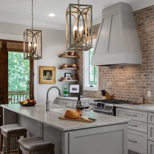 Kitchen - traditional kitchen idea in Birmingham with a farmhouse sink, marble countertops, brick backsplash, stainless steel appliances, an island, shaker cabinets, gray cabinets and gray countertops