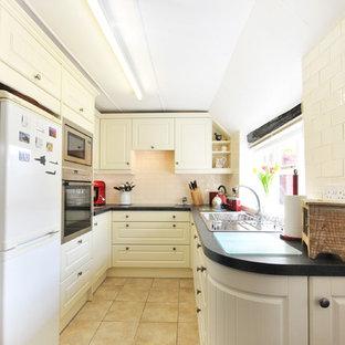 Inspiration for a farmhouse ceramic floor kitchen remodel in Kent with a drop-in sink, beige backsplash, subway tile backsplash and stainless steel appliances