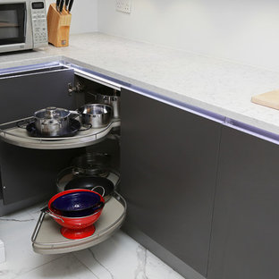 Example of a small minimalist kitchen design in London with flat-panel cabinets, gray cabinets and stainless steel appliances