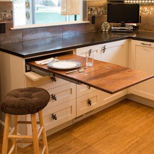 サンフランシスコの小さいエクレクティックスタイルのおしゃれなキッチン (エプロンフロントシンク、シェーカースタイル扉のキャビネット、ベージュのキャビネット、ガラスタイルのキッチンパネル、シルバーの調理設備の、竹フローリング、アイランドなし) の写真