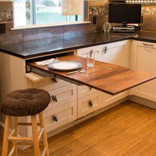 This is an example of a small eclectic u-shaped separate kitchen in San Francisco with a farmhouse sink, shaker cabinets, beige cabinets, glass tile splashback, stainless steel appliances, bamboo floors and no island.
