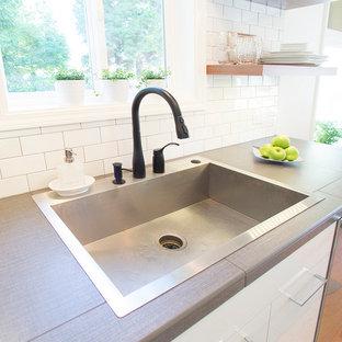 ポートランドの小さいビーチスタイルのおしゃれなキッチン (ドロップインシンク、フラットパネル扉のキャビネット、白いキャビネット、タイルカウンター、白いキッチンパネル、サブウェイタイルのキッチンパネル、シルバーの調理設備、淡色無垢フローリング、アイランドなし) の写真
