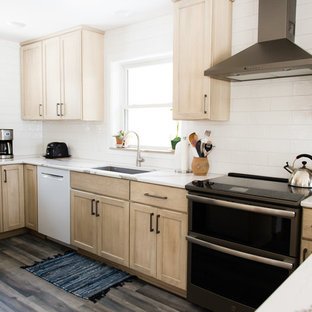 This is an example of a mid-sized transitional u-shaped separate kitchen in Other with an undermount sink, flat-panel cabinets, beige cabinets, quartz benchtops, white splashback, subway tile splashback, black appliances, vinyl floors, a peninsula, brown floor and white benchtop.