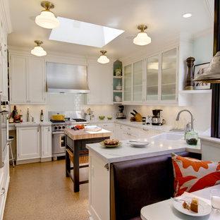 Exempel på ett klassiskt kök, med skåp i shakerstil, vita skåp, vitt stänkskydd, stänkskydd i tunnelbanekakel, rostfria vitvaror, en rustik diskho, marmorbänkskiva och korkgolv