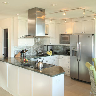 This is an example of a small beach style u-shaped eat-in kitchen in Charleston with a drop-in sink, raised-panel cabinets, white cabinets, wood benchtops, metallic splashback, glass tile splashback, stainless steel appliances, cement tiles, no island, beige floor and grey benchtop.