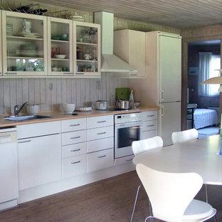 Immagine di una cucina rustica con ante di vetro, ante bianche, elettrodomestici bianchi e lavello da incasso