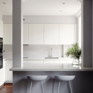 Design ideas for a small contemporary kitchen in London with a submerged sink, flat-panel cabinets, white cabinets, a breakfast bar, brown floors, grey splashback, black appliances and dark hardwood flooring.