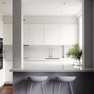 На фото: маленькая кухня в современном стиле с врезной раковиной, плоскими фасадами, белыми фасадами, полуостровом, коричневым полом, серым фартуком, черной техникой и темным паркетным полом с