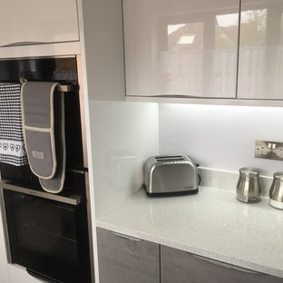 バッキンガムシャーの小さいモダンスタイルのおしゃれなキッチン (アンダーカウンターシンク、フラットパネル扉のキャビネット、白いキャビネット、珪岩カウンター、グレーのキッチンパネル、ガラス板のキッチンパネル、パネルと同色の調理設備、アイランドなし、白いキッチンカウンター) の写真