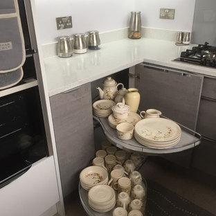 バッキンガムシャーの小さいモダンスタイルのおしゃれなキッチン (アンダーカウンターシンク、フラットパネル扉のキャビネット、グレーのキャビネット、珪岩カウンター、グレーのキッチンパネル、ガラス板のキッチンパネル、パネルと同色の調理設備、クッションフロア、アイランドなし、白いキッチンカウンター) の写真