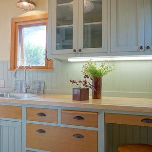 サンディエゴのビーチスタイルのおしゃれなII型キッチン (ドロップインシンク、フラットパネル扉のキャビネット、緑のキャビネット、木材カウンター、緑のキッチンパネル、木材のキッチンパネル、淡色無垢フローリング、茶色いキッチンカウンター) の写真