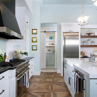 チャールストンの大きいトランジショナルスタイルのおしゃれなキッチン (ドロップインシンク、フラットパネル扉のキャビネット、ターコイズのキャビネット、クオーツストーンカウンター、白いキッチンパネル、セラミックタイルのキッチンパネル、シルバーの調理設備の、無垢フローリング、茶色い床、白いキッチンカウンター) の写真