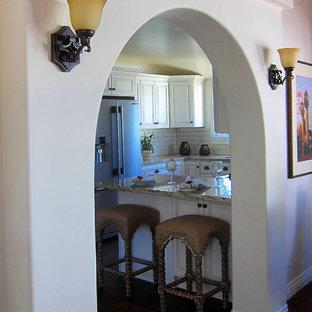 サンタバーバラの小さい地中海スタイルのおしゃれなキッチン (アンダーカウンターシンク、レイズドパネル扉のキャビネット、御影石カウンター、シルバーの調理設備の、無垢フローリング、白いキャビネット、茶色い床、ベージュのキッチンカウンター) の写真