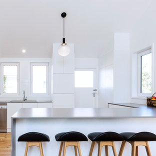Inspiration for a small contemporary u-shaped open plan kitchen in Canberra - Queanbeyan with an undermount sink, flat-panel cabinets, white cabinets, laminate benchtops, white splashback, porcelain splashback, stainless steel appliances, medium hardwood floors, a peninsula, grey benchtop and brown floor.