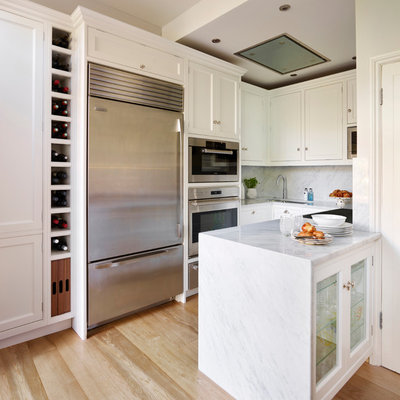 Inspiration for a small transitional u-shaped light wood floor kitchen remodel in Hertfordshire with beaded inset cabinets, white cabinets, white backsplash, stone slab backsplash, stainless steel appliances and a peninsula