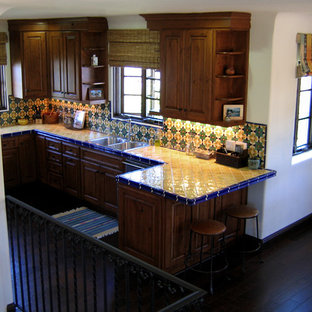 Inspiration for a small mediterranean u-shaped eat-in kitchen in Santa Barbara with a double-bowl sink, raised-panel cabinets, medium wood cabinets, tile benchtops, ceramic splashback, stainless steel appliances, dark hardwood floors, a peninsula, multi-coloured splashback, brown floor and yellow benchtop.