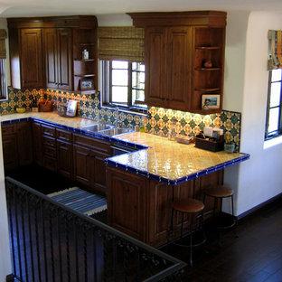 Inspiration för små medelhavsstil gult kök, med en dubbel diskho, luckor med upphöjd panel, skåp i mellenmörkt trä, kaklad bänkskiva, stänkskydd i keramik, rostfria vitvaror, mörkt trägolv, en halv köksö, flerfärgad stänkskydd och brunt golv
