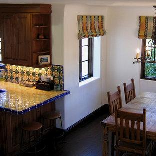 Источник вдохновения для домашнего уюта: маленькая п-образная кухня в средиземноморском стиле с обеденным столом, двойной раковиной, фасадами с выступающей филенкой, фасадами цвета дерева среднего тона, столешницей из плитки, фартуком из керамической плитки, техникой из нержавеющей стали, темным паркетным полом, полуостровом, разноцветным фартуком, коричневым полом и желтой столешницей