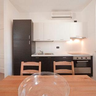 ミラノの小さいモダンスタイルのおしゃれなキッチン (ダブルシンク、フラットパネル扉のキャビネット、濃色木目調キャビネット、ラミネートカウンター、白いキッチンパネル、シルバーの調理設備、セラミックタイルの床、アイランドなし) の写真