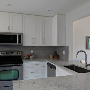 This is an example of a small transitional u-shaped eat-in kitchen in Vancouver with a single-bowl sink, shaker cabinets, white cabinets, quartz benchtops, grey splashback, ceramic splashback, stainless steel appliances, vinyl floors, no island, beige floor and grey benchtop.