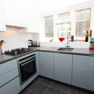 ロンドンのモダンスタイルのおしゃれなキッチン (ガラス扉のキャビネット、青いキャビネット、珪岩カウンター、シルバーの調理設備、アイランドなし) の写真