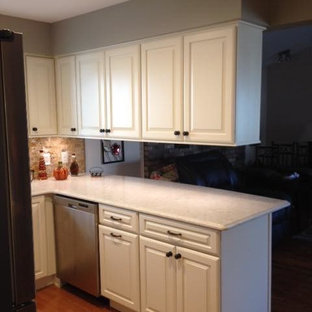 Photo of a small traditional u-shaped eat-in kitchen in Detroit with an undermount sink, raised-panel cabinets, white cabinets, quartz benchtops, brown splashback, slate splashback, stainless steel appliances, light hardwood floors, a peninsula and brown floor.