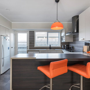 Photo of a small contemporary u-shaped eat-in kitchen in Auckland with an undermount sink, flat-panel cabinets, beige cabinets, a peninsula, laminate benchtops, multi-coloured splashback, ceramic splashback, white appliances, ceramic floors and multi-coloured floor.