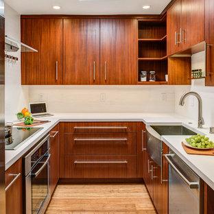 Foto di una piccola cucina design con lavello stile country, ante lisce, ante in legno bruno, top in superficie solida, paraspruzzi bianco, paraspruzzi in gres porcellanato, elettrodomestici in acciaio inossidabile, pavimento in bambù e nessuna isola